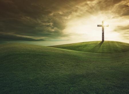 Kruis op de top van de heuvel bij zonsondergang Stockfoto