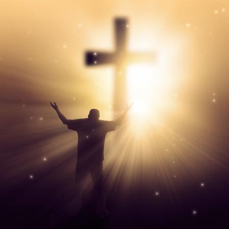 alabando a dios: Un hombre que caminaba hacia una cruz con rayos de sol Foto de archivo
