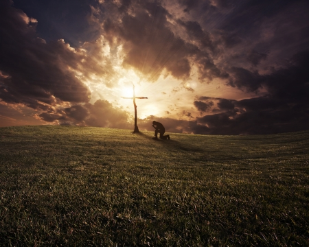 kneel: A man kneeling at a cross at sunset. Stock Photo