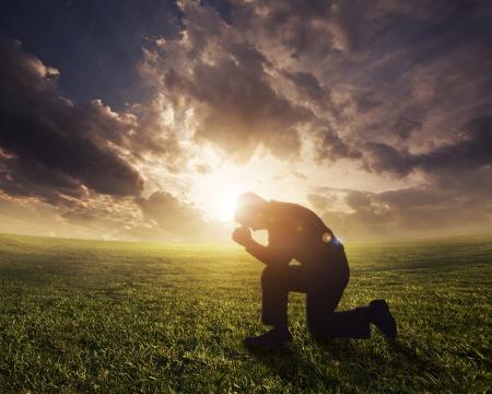 ひざまずく: 夕暮れ時に祈ってシルエットの男