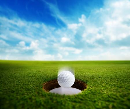 Golfbal vallen in de beker op de groene. Stockfoto