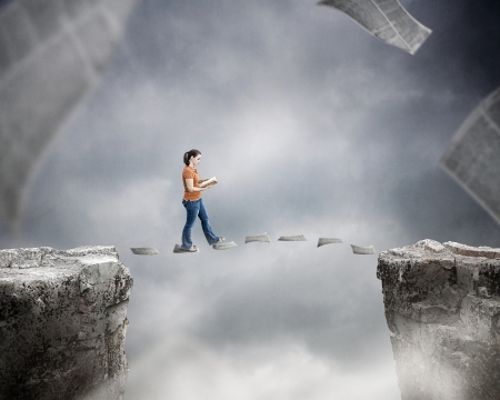 chasm: Woman reading a book and walking on pages over cliff