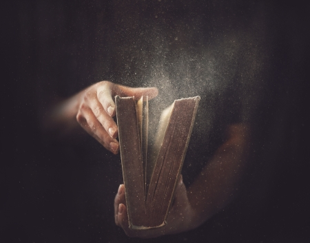 Holding an open book with dust coming out