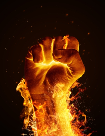 Hand consumed in flames on black background