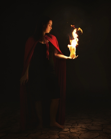 Woman holding a burning fire ball at night.