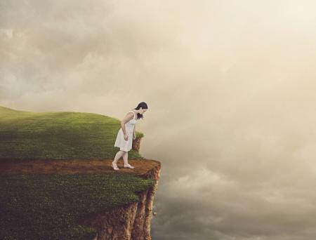 背の高い崖につながるパスを歩いて女性。 写真素材