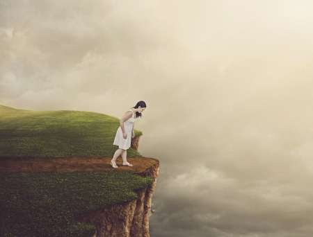 chasm: Woman walking on path that leads to a tall cliff.