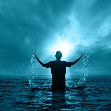bautismo: El hombre surge de las aguas durante la noche. Foto de archivo