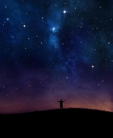 夜空の下で賞賛に彼の手を持ち上げる人。 写真素材