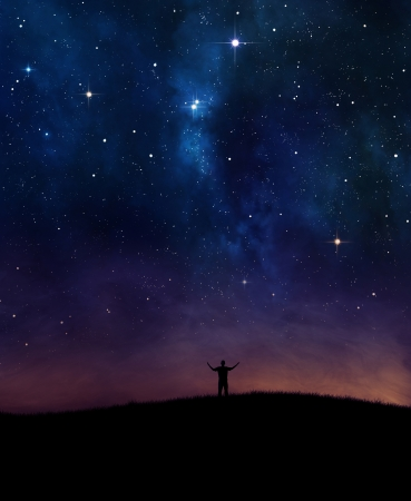 A man lifting his hands in praise under night sky.