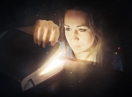 Kobieta patrząc w świecące Biblii z jasnych świateł. Zdjęcie Seryjne