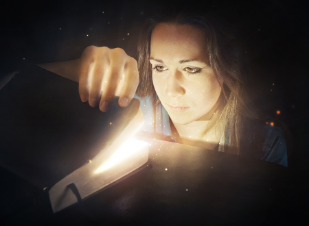 discover: Woman looking into a glowing Bible with bright lights. Stock Photo