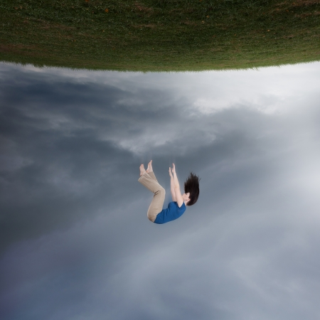 Surreal image of a woman falling up towards the sky.