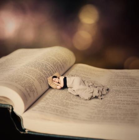 聖書のページで寝ている女性の超現実的なイメージ。 写真素材