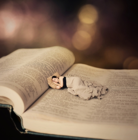 Surreal image of a woman sleeping on the pages of the Bible. Stock Photo