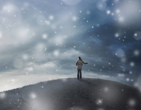 blizzard: A woman standing on top of a hill in a snow storm