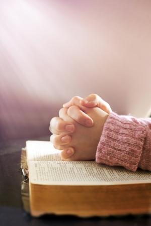 Womans hands in prayer over an open Bible