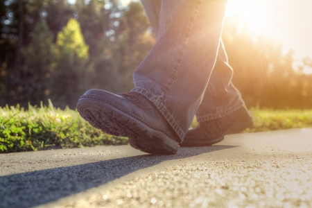 Close up of a man walking on road. photo