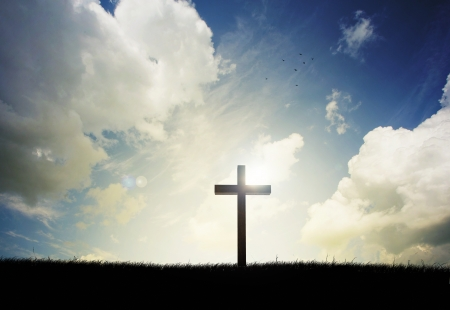 almighty: Cross on a hillside with sunset in the background. Stock Photo