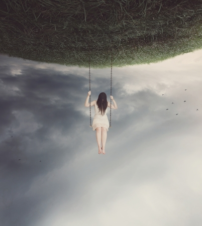 Sad woman swinging on a surreal swing. Stok Fotoğraf