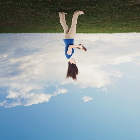 Woman reading a book with her hair falling towards the sky. Stock Photo