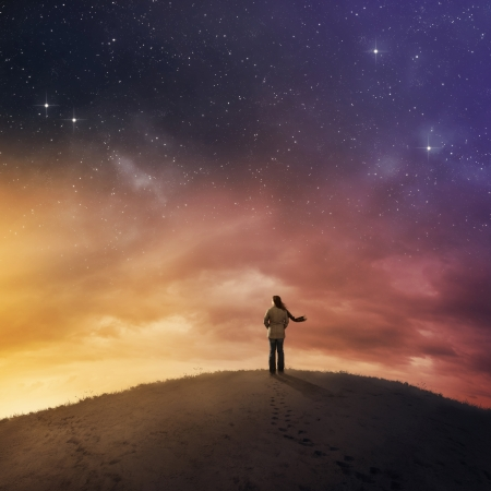 Woman standing in snow under starry night sky.