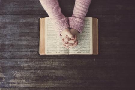 木製のテーブルの聖書を祈る女性。
