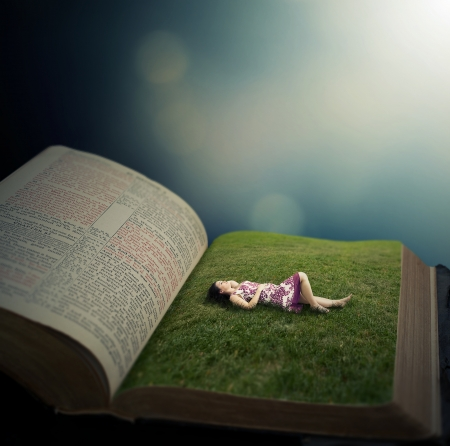 Woman laying on the pages of a Bible in a grassy field.