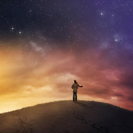 별이 빛나는 밤 하늘 아래 눈에 서있는 여자. 스톡 콘텐츠