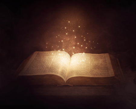 A Bible in the dark with bright glowing lights.