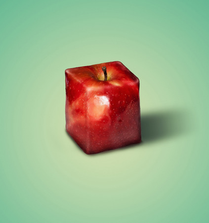 Surreal image of a square apple on a green background. Stock fotó