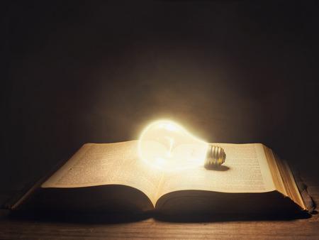 오픈 성경에 빛나는 전구의 초현실적 인 이미지. 스톡 콘텐츠