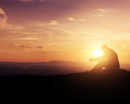 Man, die bidt als de zon opkomt in de bergen. Stockfoto