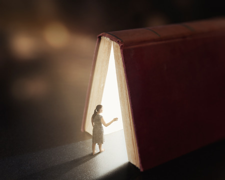 bible book: Woman is lost and wanders into a book with glow lights. Stock Photo