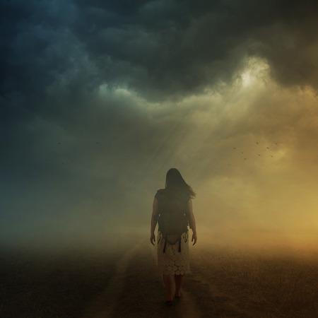 霧の真ん中に歩道を歩いて女性。