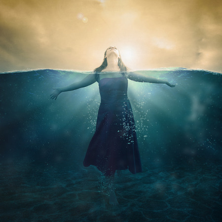 waters: A woman standing in the deep waters with her head above the surface. Stock Photo