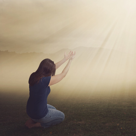 lift hands: A woman on her knees in worship in a field. Stock Photo