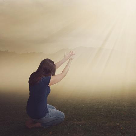 prayer hands: Una donna in ginocchio in adorazione in un campo. Archivio Fotografico