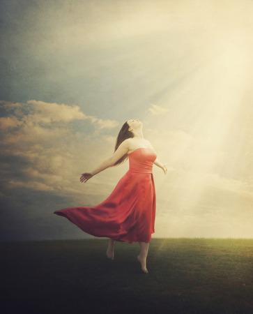 太陽光線のグランジ背景に下って来るとフィールドに立っている女性。 写真素材