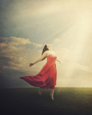 A woman standing in a field with sun rays coming down on a grunge background.