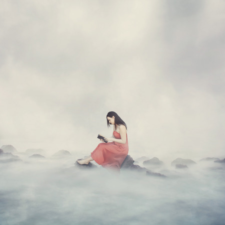Woman alone on top of the clouds reading her Bible.