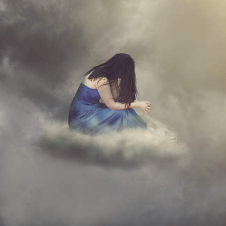 Woman praying alone while sitting on a cloud.