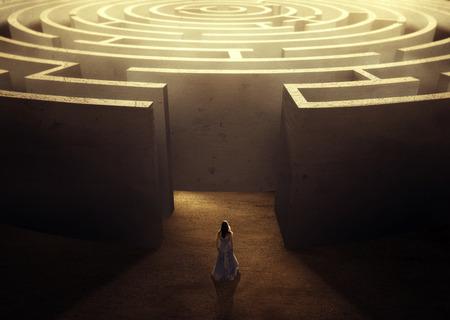 Una donna che indossa un abito cercando di fare la sua strada attraverso un grande labirinto.