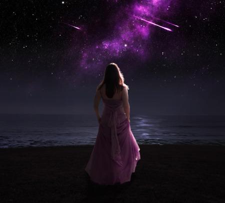 사격: 유성을보고 밤에 드레스에 서있는 여자. 스톡 사진
