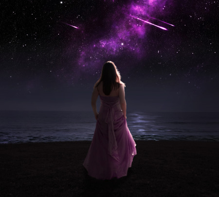 surreal: Woman standing in dress at night watching shooting stars.