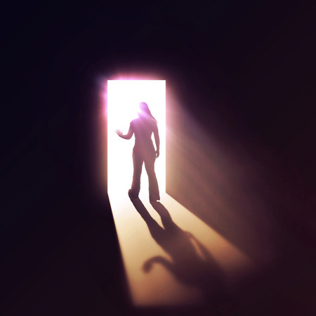 tunnels: Woman walking through a bright and glowing doorway. Stock Photo