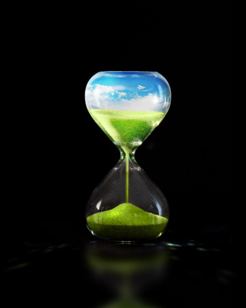 An hourglass on a black background with a green meadow falling apart. photo