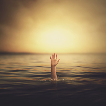 coming out: A hand coming up out of the water looking for help. Stock Photo