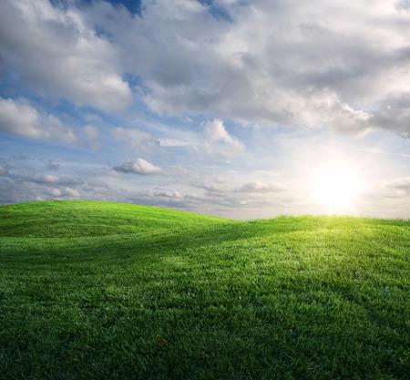 美しい太陽と緑の草が茂った草原の上の雲。
