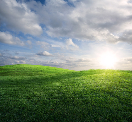 Beautiful sun and clouds over a green grassy meadow.